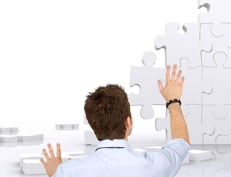 Business man building a puzzle isolated over white