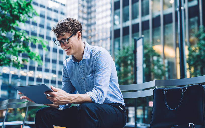 man-sits-on-bench-and-looks-at-tablet