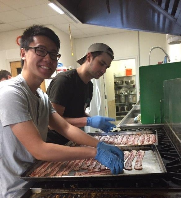 Ryan and Liam making bacon for the YWCA breakfast. Ryan is at least looking at the camera