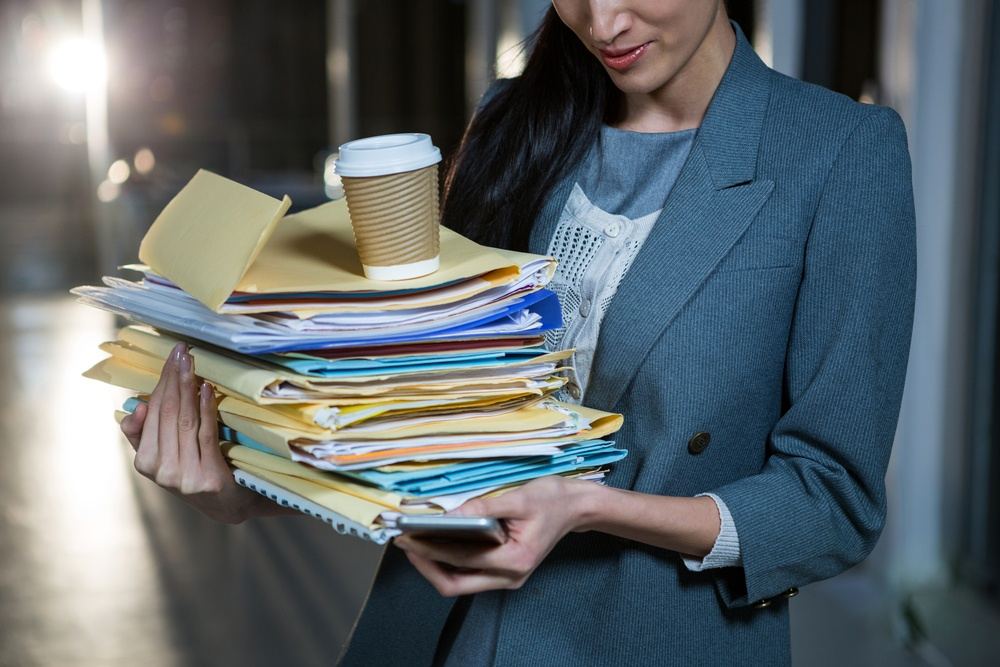 Businesswoman carrying stack of file folders while using mobile phone in the office