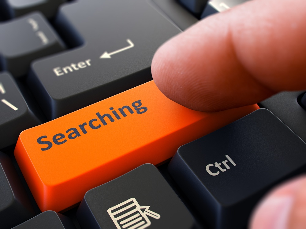 Searching Button. Male Finger Clicks on Orange Button on Black Keyboard. Closeup View. Blurred Background.